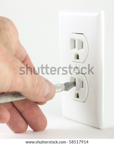 A dangerous situation can occur when putting foreign objects into an electrical outlet, like electrocution - stock photo