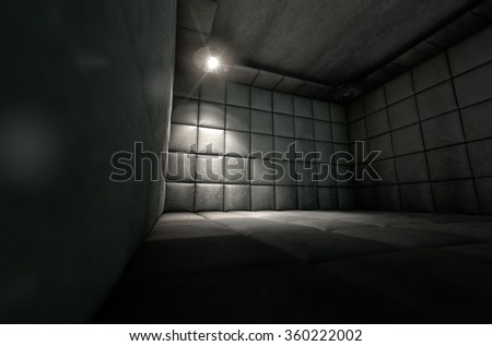 A dark dirty white padded cell in a mental hospital with a corner lit by a single spotlight - stock photo