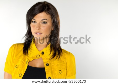 A dark haired model wearing yellow on a white background