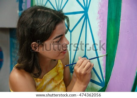 A dark-haired woman is painting a mystic picture on a wall