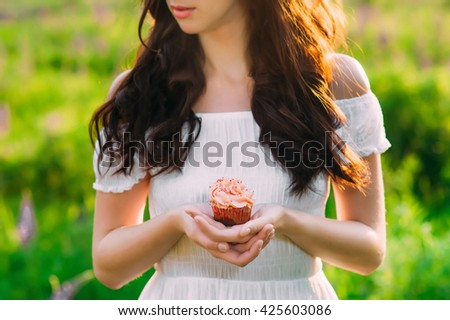 a dark haired young girl holding a pink-creamed muffin in her gentle hands - stock photo