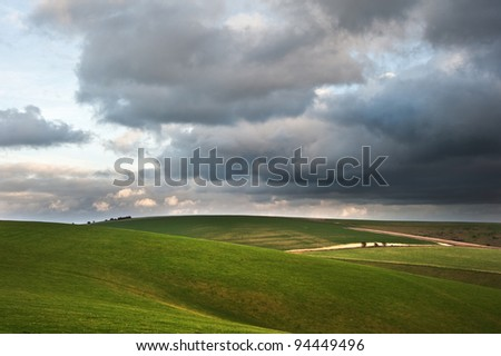 A dark sky forms over lush green rolling English countryside landscape - stock photo
