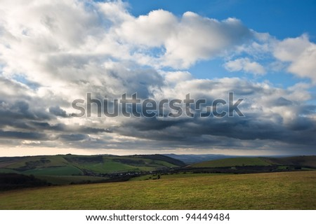 A dark sky grows over English countryside landscape - stock photo