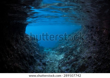 A dark, submerged cave looks out on sunlit blue water in the tropical Pacific Ocean. Many species that do not like sunlight live in the dark recesses of caves and caverns. - stock photo