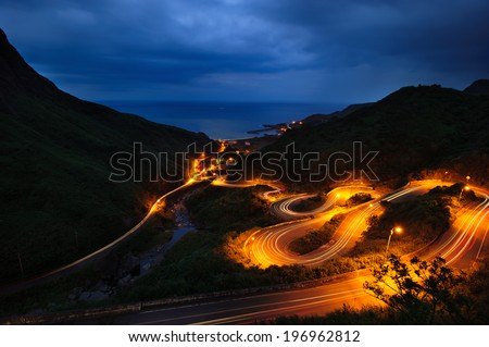 A dark windy road illuminated by street lights. - stock photo