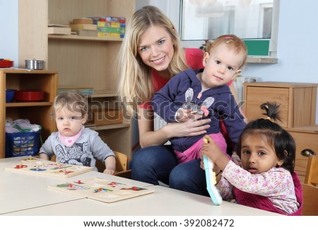 A Day care or kindergarten kids and teacher playing with a puzzle - stock photo