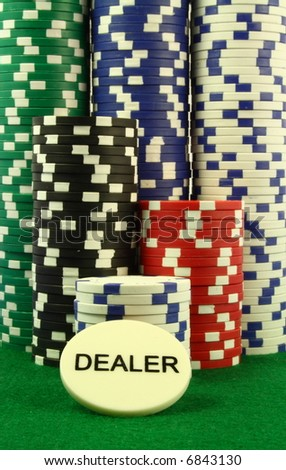 a dealer chip in  front of several piles of poker chips on a green table.