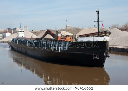 A deck barge powered by a tugboat moves up the Cuyahoga River in Cleveland, Ohio past mounds of aggregate material used to make concrete - stock photo