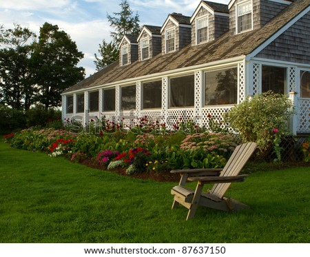A deck chair in the morning sun on a grass lawn in front of a beautiful home and garden. - stock photo