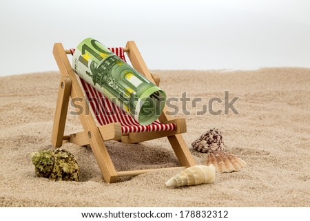 a deck chair with a euro banknote. symbolic photo for saving on holiday and when traveling - stock photo