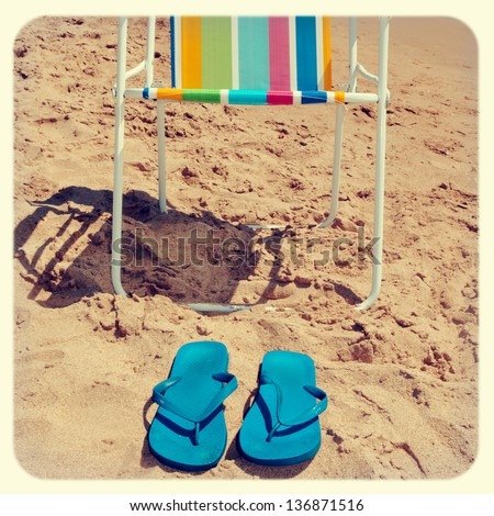 a deckchair and a pair of flip-flops on the beach, with a retro effect - stock photo