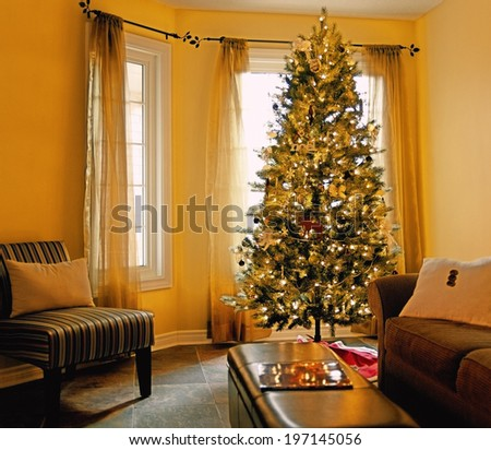 A decorated Christmas tree in a living room. - stock photo