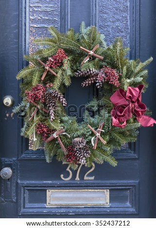 A decorative Christmas wreath on the door of an old house.