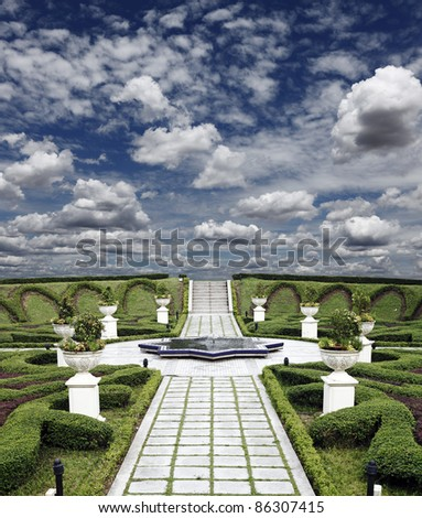 A decorative pathway through a manicured green garden with an ornate fountain against a dramatic blue cloudy sky. - stock photo
