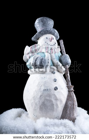 A decorative snowman in the dark, cold outdoors during the holiday season. - stock photo