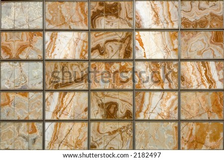 A decorative squared wall with marble slabs - stock photo
