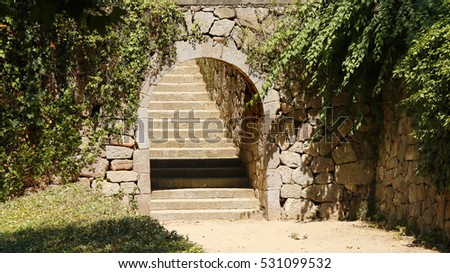 A decorative vintage stone arc and a stairway in a park