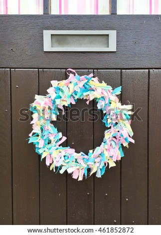 A decorative wreath on a black wooden door