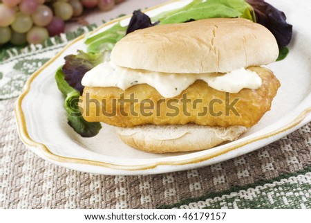 A deep fried fish sandwich on a bun with tarter sauce, horizontal with selective focus and copy space - stock photo