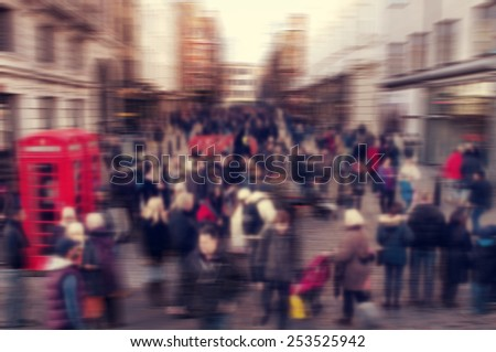 a defocused blur background of people walking in a street in London, United Kingdom - stock photo