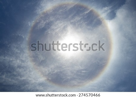 A 22 degree halo of sunlight refracted through ice crystals in thin cirrus clouds in the atmosphere.  The colours of the rainbow are just visible.  - stock photo