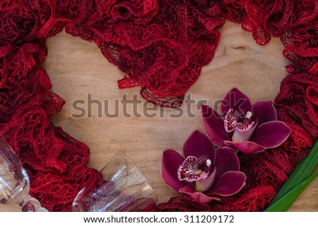 A delicate, red, heart shape on a wooden background with a couple red orchids and glasses. Great photo for valentines day, wedding invitations, or other creative ideas and concepts. Horizontal format. - stock photo