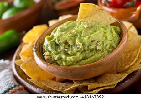 A delicious authentic mexican guacamole dip with avocado, lime, and tomato. - stock photo