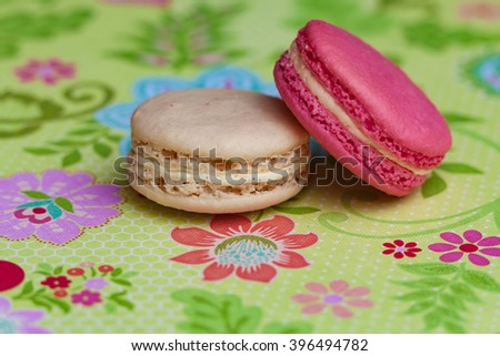 A delicious collection French Macaron Pastries - Rose, Jasmine Green Tea, Vanilla and Chocolate.  Set with colorful paper backgrounds and ceramic bowls, tea cups and plates