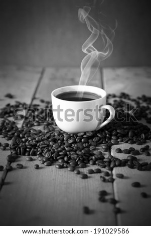 A delicious cup of coffee on a table with roasted coffee beans in black and white - stock photo