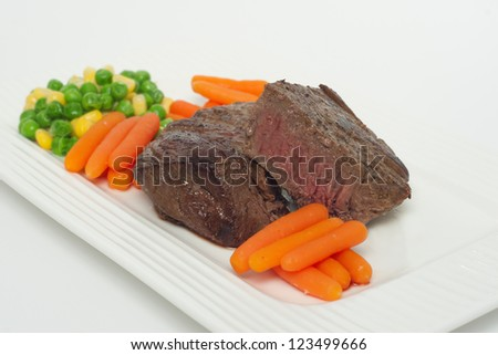 A delicious filet with carrots on a white dish - stock photo