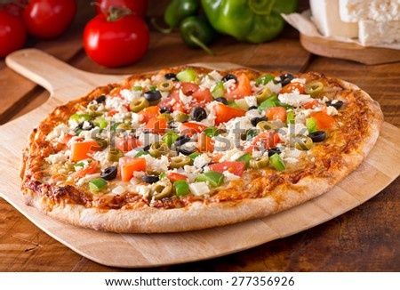 A delicious freshly baked greek pizza with feta cheese, olives, tomato, and green pepper. - stock photo