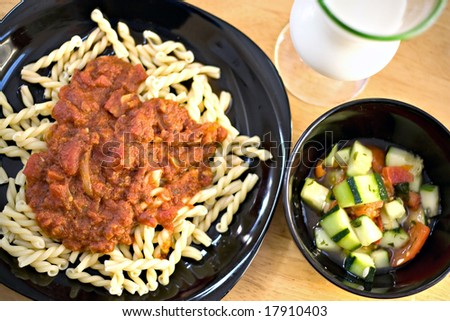 A delicious homemade Italian meal. Gemelli pasta with fresh homemade marinara sauce along with a cucumber tomato salad. - stock photo