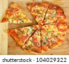 A delicious homemade pizza on a wooden chopping board. - stock photo