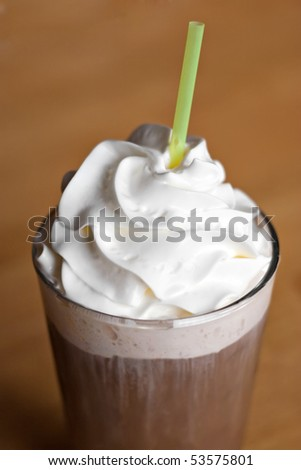 A delicious iced coffee drink topped with fresh whipped cream.  Shallow depth of field. - stock photo