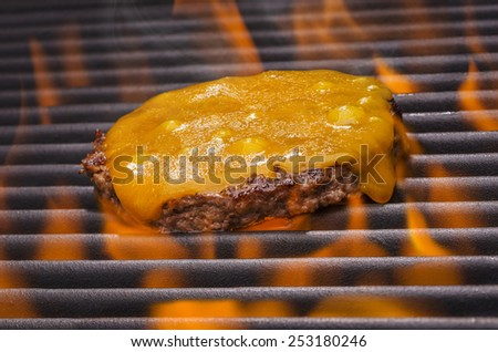 A Delicious Juicy Cheeseburger on a Flaming BBQ Grill - stock photo