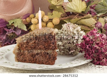 A delicious moist slice of a homemade double layer German Chocolate Cake on a plate with one pink unlit candle, with vintage decorations, horizontal with copy space