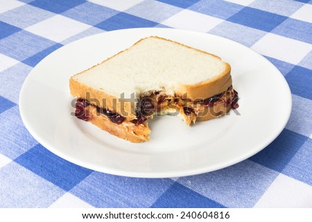 A delicious peanut butter and jelly sandwich with grape jam has a bite taken out of it during lunchtime.  - stock photo