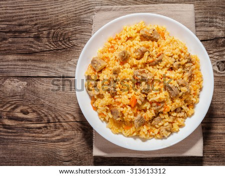 A delicious pilaf in a dish on the old board.
