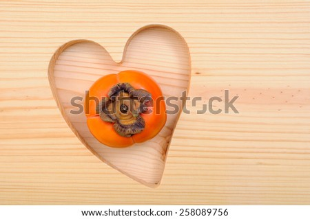 a delicious ripe persimmon  in heart shape wooden tray - stock photo