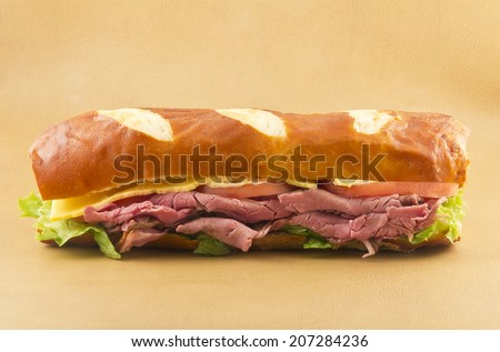 A delicious roast beef sandwich on a pretzel bun - stock photo