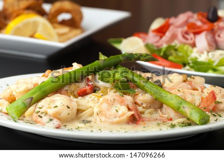 A delicious shrimp scampi pasta dish with fried shrimp and antipasto salad in the background. - stock photo