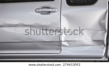 A dent in the side of a car - stock photo