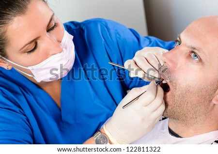 A dentist carrying out a dental examination - stock photo