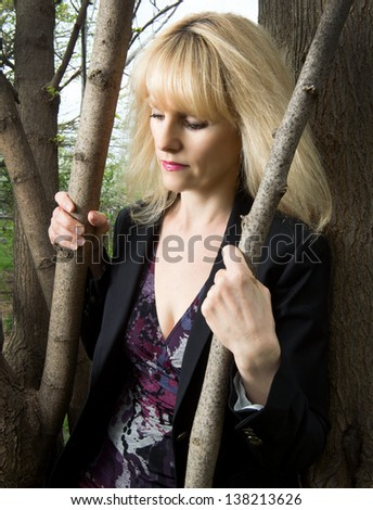 A depressed business woman  takes a moment to herself gripping a tree outside the office . - stock photo