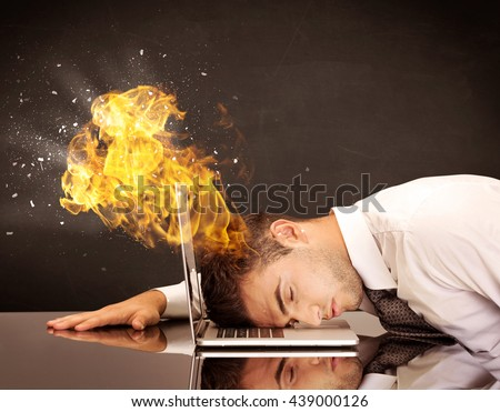 A depressed businessman banging his head in a keyboard and shouting with his head on fire, reflecting on desk - stock photo