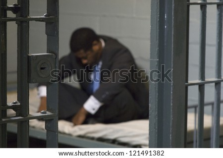 A depressed businessman sitting in jail - stock photo
