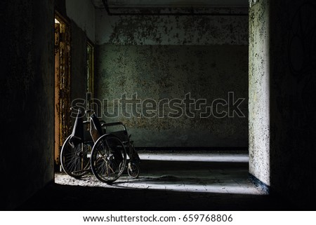 A derelict wheelchair inside an abandoned hospital.