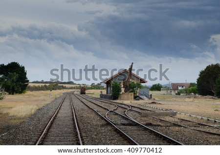 A deserted train station in a small Australian town, against a dramatic sky