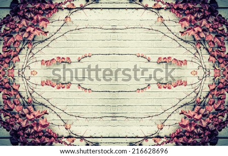 A design of stylized from real grape vines and autumn red leaves in the center and border of a gray brick wall.  Room for copy space.  Filtered for a vintage retro look. - stock photo
