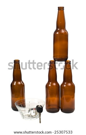 A designated driver placed his keys into a glass bowl, with empty beer bottles beside them - stock photo